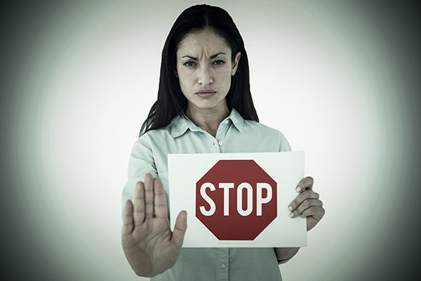 frowning woman with hand held up and holding stop sign